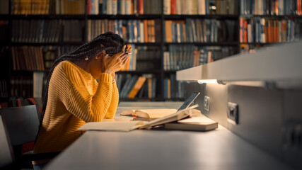 University Library: Exhausted and Tired Black Girl uses Laptop, Writes Essay, Study for Class Assignment. Students Learning, Studying for Exams College. Side View Portrait with Bookshelves