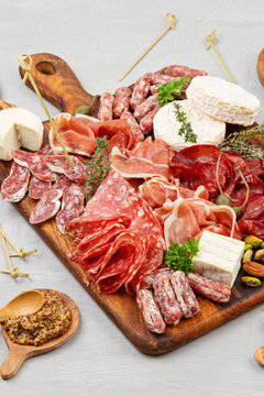 Appetizers table with differents antipasti, charcuterie, snacks and wine. Sausage, ham, tapas, olives, cheese and crackers for buffet party. Top view