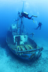Scuba Divers Exploring underwater ship wreck
