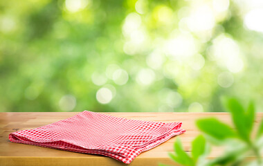 Aluminium Prints Picnic Red checked tablecloth on wood with blur green bokeh of tree background