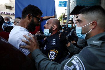 A man argues with a policeman during a demonstration against the oppression of black people in the U.S, the aggression of Israeli forces against Palestinians and domestic violence, in Jerusalem