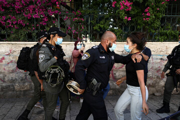 A woman is pushed by an Israeli policeman during a demonstration against the oppression of black people in the U.S, the aggression of Israeli forces against Palestinians and domestic violence, in Jerusalem