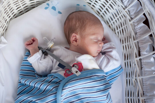 A premature baby sleeps on a moses basket.
