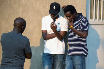 Civilians gather to listen to news updates from a radio receiver in Bujumbura