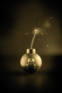 A bomb with a lit fuse on a dark background. Skull and bones. Detonation. Explosion hazard.