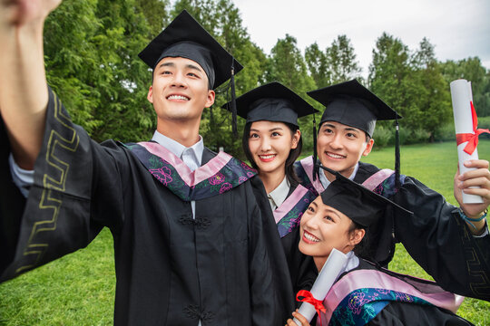 With four college students wearing bachelor's clothing