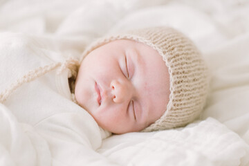 Newborn baby in knit bonnet sleeping on white bed