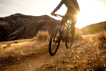 Woman mountain biking during sunset in mountains on single track