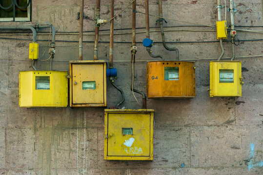 yellow electricity meters on the wall of a residential building close-up
