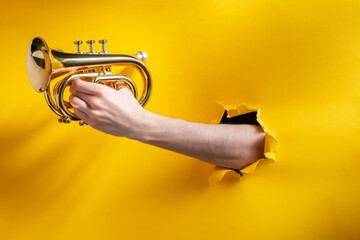 Spoed Foto op Canvas Muziekwinkel Hand playing horn through a torn hole in yellow paper background