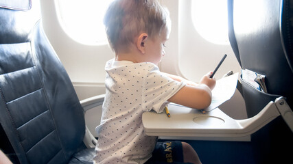 Cute little boy drawing picture with pencils while flying in airplane