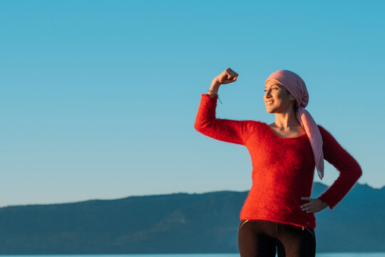 Healthy woman showing her fist of power against female cancer