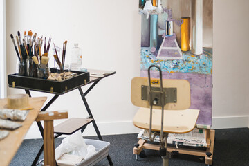 Table with various tools for painting paintbrushes and wooden easel with colorful oil painting in creative modern interior of cozy art workshop