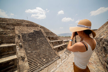 Side view of young anonymous female traveler in casual clothes and straw hat taking pictures of old ancient stone stairs with photo camera while visiting sunny Mexico