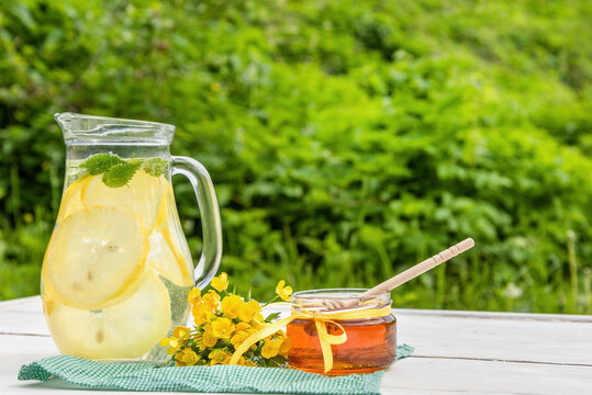 A jug of mint lemonade and a jar of honey on the table in the summer green garden.