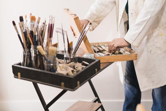 Senior artist standing in home workshop and choosing paints