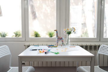 Watercolor palette with colored pencils and colorful kids drawings on white table with chairs on sides at wooden floor