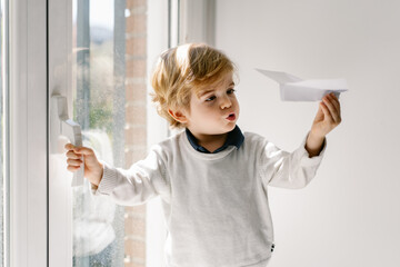 Happy blond child in casual clothes playing with paper airplane while sitting barefoot on window sill on sunny day