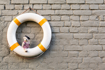 Seaside Wall Decoration / Vintage life buoy at brick wall background and cute little teddy bear wear nostalgic sailor swimsuit sit on it (copy space)