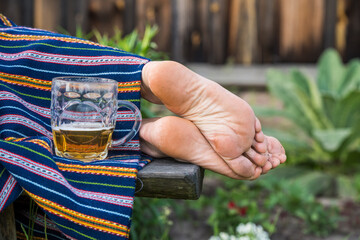 Glass of light beer and woman bare feet, Ligo