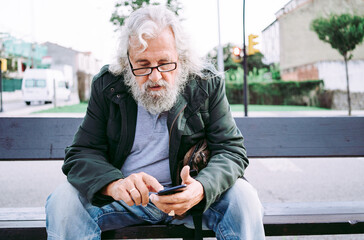 Concentrated grey bearded man in casual clothes wearing eyeglasses and messaging on mobile phone while resting on street bench