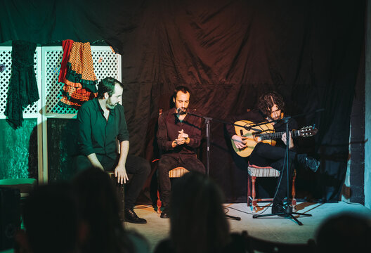 Band of Hispanic male musicians in black wear sitting on wooden chairs while playing acoustic guitar and singing flamenco song into microphone on theater stage in public
