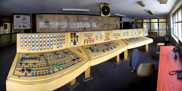 Yellow old dashboards with many buttons sensors and dials in control room with drawings and diagrams on wall in deserted building of neglect coal mine