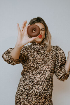 Young female in dress with leopard print pouting lips and looking at camera through sweet chocolate doughnut against gray background