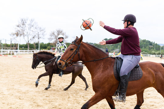 Teen boys in helmets throwing ball to each other while riding horses on dressage arena during lesson in equestrian school