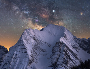 Amazing view of white snowy mountain range under incredible night starry sky in winter evening