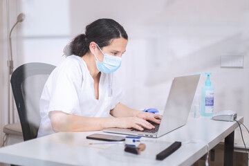 Serious young female doctor wearing white uniform and medical mask working on laptop in latex gloves sitting at desk in modern clinic