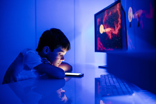 Side view of confused boy watching cellphone empty screen and touching head while sitting in room with blue light at home