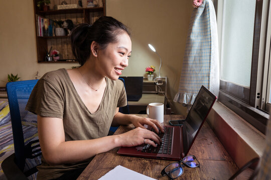 Side view of Asian female freelancer in casual t shirt and eyeglasses sitting at table and browsing computer while working on project online at home