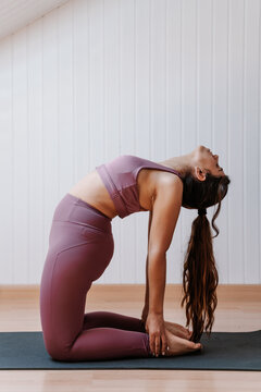 Young female woman in sportswear performing stretching exercise while working out during yoga session at home