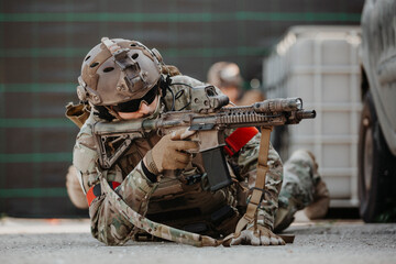 Soldier aiming airsoft gun during tactical game