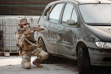 Adult man in military uniform aiming and shooting gun while lying on ground near vehicle during airsoft match