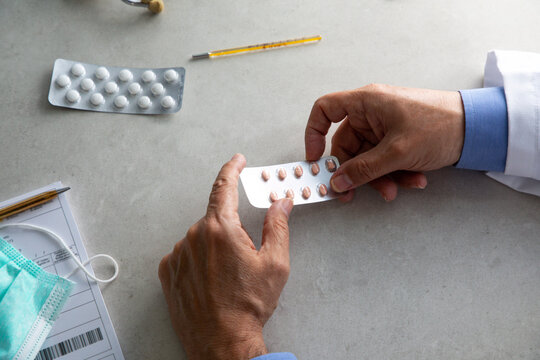 Top view of crop unrecognizable male practitioner in white gown sitting at table with packs of pills and working in clinic during COVID 19 outbreak