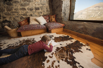Boy lying on floor on cozy carpet and drawing with colored pencils in sketchbook chilling cozy living room of stone house in Cantabria
