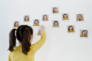 Cute little girl in a yellow dress is standing on her back placing photos of herself showing various emotions