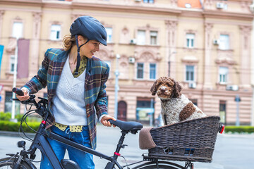 young woman pushing her electric bicycle with the dog in the basket