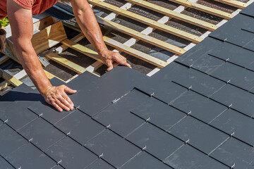 Craftsmen are installing a slate roof home.Professional roof workers repairing roof t.Working on rooftop.