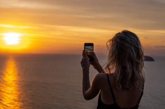 Woman hands holding mobile phone at sunset. Young curly hair woman taking photos with her cell phone in a beautiful amazing sunset over sea. Taking a picture on a smartphone during a vacation