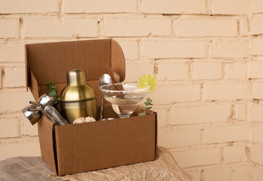 Stay at home bar cocktail party. Classic Margarita cocktail and bartender stuff parcel in a brown craft cardboard box. Gift to mixology lover. Beige brick wall background. Tender retro hipster colors