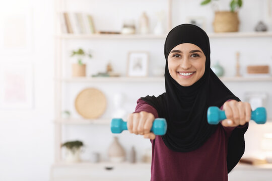 Smiling muslim girl in hijab exercising with dumbbells at home