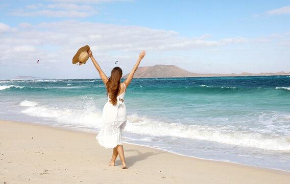 Freedom happy girl enjoying wind with raised arms and people kitesurfering, Corralejo Dunes beach, Fuerteventura, Canary Islands