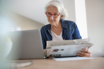 Senior woman reading newspaper in front of laptop