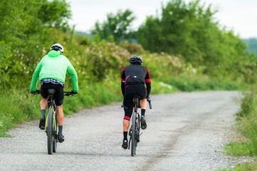 Two bikers with mountain bikes on a gravel road