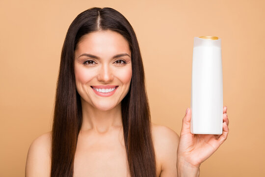 Close-up portrait of her she nice-looking attractive lovely shine pretty cheerful cheery long-haired woman holding in hand natural oil balm bottle isolated over beige pastel color background