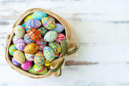 Many of colorful painted easter eggs on basket on old white wood table with free copy space for texts.