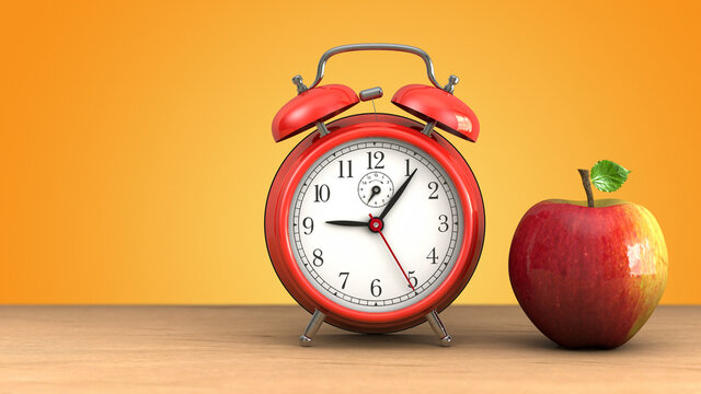 Retro red alarm clock at about 9 o'clock and apple on wood against orange background.